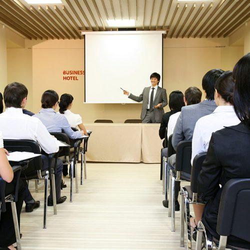 Image of confident businessman explaining something on whiteboard during conference